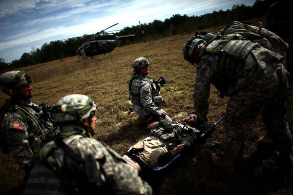 U.S. troops wait for the signal to bring a injured Afghan soldier out to a waiting helicopter.