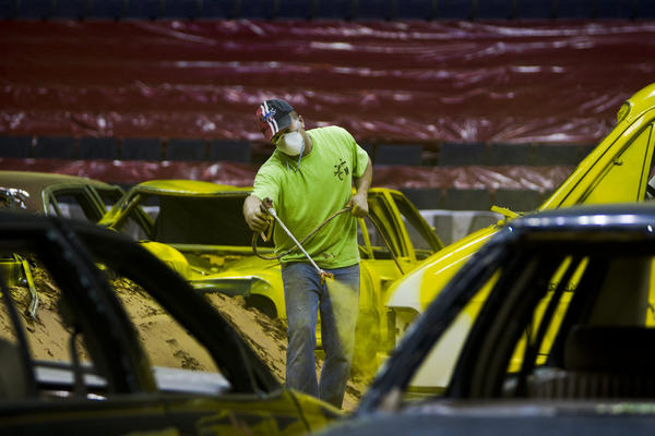 After laying down a 10,000-yard stockpile of dirt with an 8- to 10-inch base, the constructing of the obstacles begin. Junkyard cars from towing companies are brought to the arena and painted over with vibrant colors to enhance the audience experience.