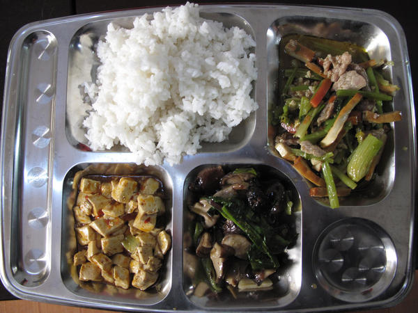 On a recent day, the children receive a tray full of rice, stir-fried pork with celery, spicy tofu and greens with mushrooms.
