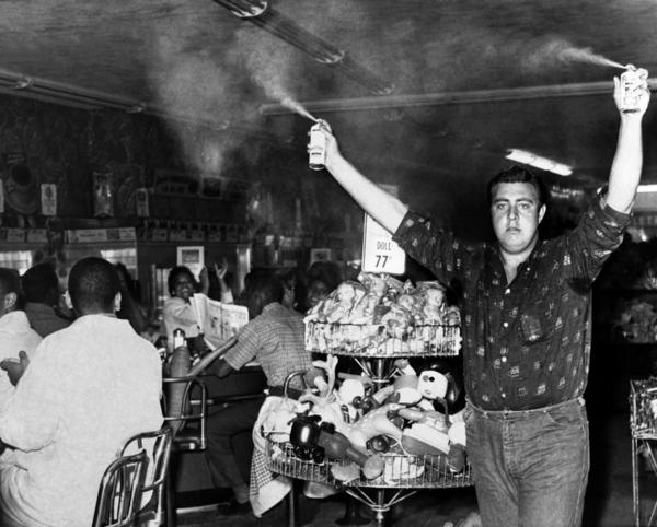 A white youth sprays insect repellent above the heads of nearly 100 African-Americans demonstrating at a lunch counter in Atlanta.