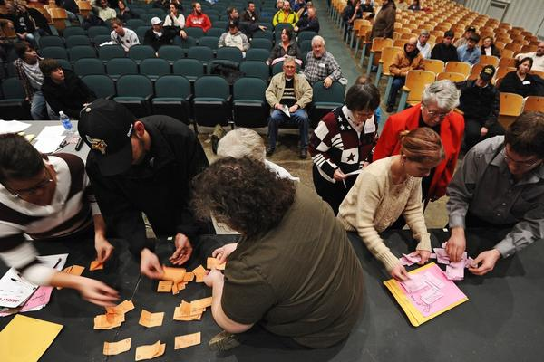 Electoral personnel and volunteers count caucus ballots at a school in Des Moines.