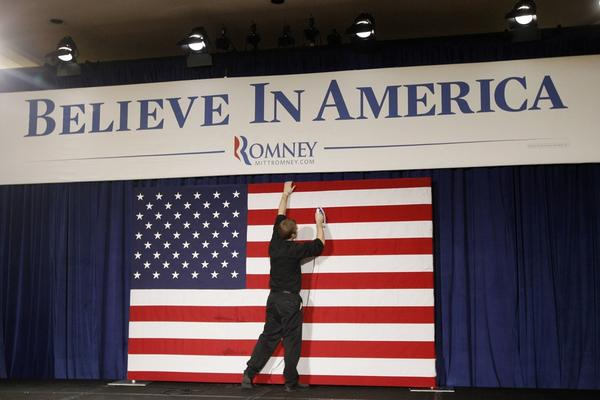 Richie Beanan irons the flag before a rally for Mitt Romney, in Des Moines.