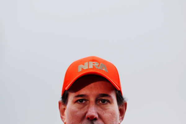 Former Sen. Rick Santorum dons a National Rifle Association hat while talking to reporters at Doc's Hunt Club in Adel, Iowa, on Dec. 26.