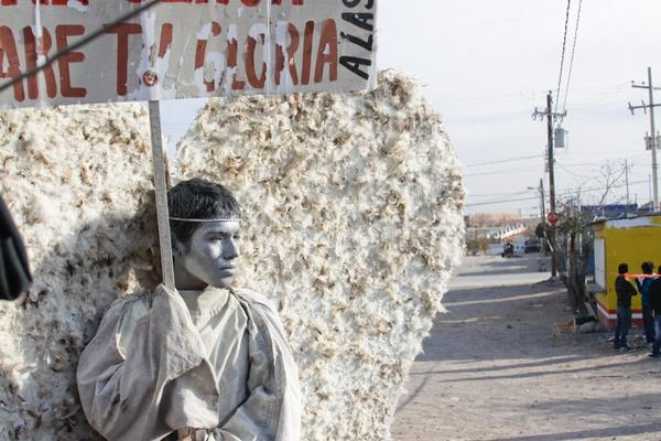 """Young members of the evangelical church Psalm 100 in Ciudad Juarez dress as """"messenger angels"""" to silently protest the Mexican city's ongoing violence. Here, 15-year-old Adan Ubacio Lopez holds a sign that translates to """"Behold, I am here, Lord. I will bear your glory."""""""