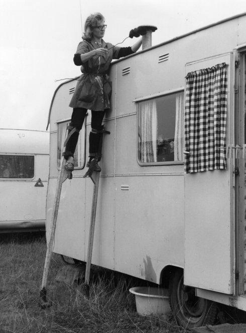 Stilt walker Joy Sloan cleans the chimney of a trailer belonging to a member of British showman Billy Smart's circus in 1963.