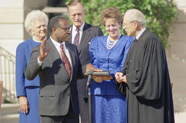 Supreme Court Justice Byron R. White administers the constitutional oath to Thomas in front of President Bush and his wife, Barbara, during a ceremony at the White House on Oct. 19.