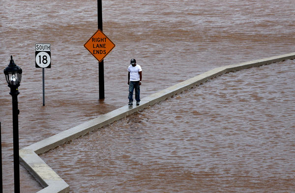 A man walks on top of a wall next to a flooded highway in New Brunswick, N.J., on Sunday.