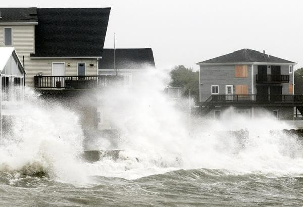 Waves crash along a seawall as the tropical storm, downgraded from a hurricane, slammed into Fairhaven, Mass., on Sunday.