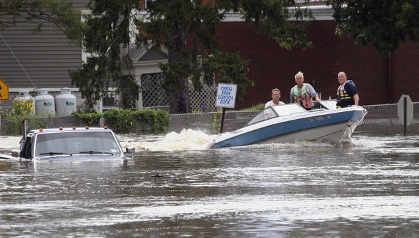 A motorboat passes a submerged pickup truck on Main Street in Washingtonville, N.Y., on Sunday following heavy rains from Tropical Storm Irene.