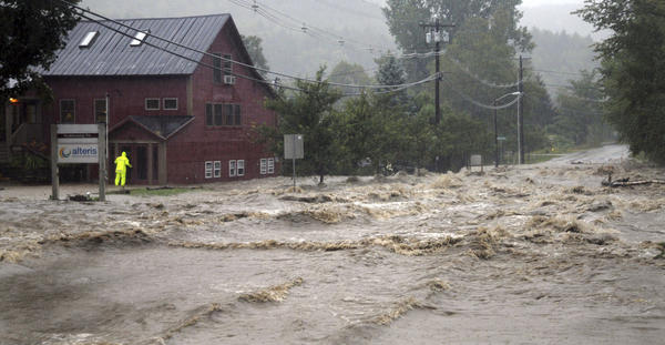A person checks a building for occupants as raging floodwaters cross Route 100, closing the main road in Waitsfield, Vt., on Sunday.