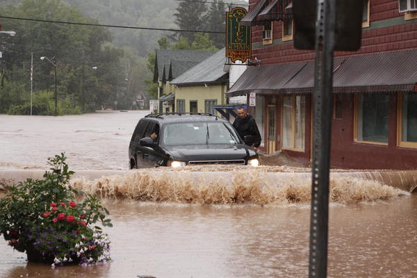 A security guard hangs on the door of Gov. Andrew Cuomo's SUV in the middle of a flooded street Sunday in Margaretville, N.Y.