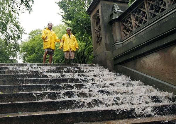 Jimmy Kaplow (left) and David Korostoff watch as water in New York City's Central Park flows down the steps as the tropical storm passes through the city on Sunday.