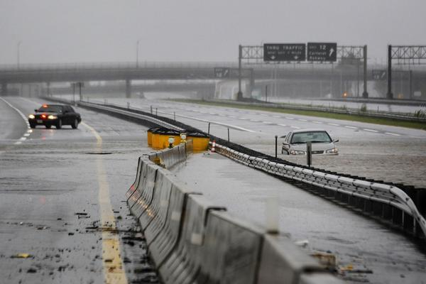 An abandoned car sits half-submerged in floodwaters on a southbound lane of the New Jersey Turnpike near exit 12 in Carteret, N.J.