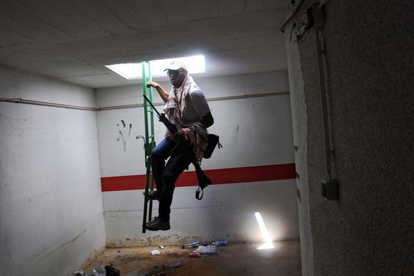 A rebel fighter enters a bunker of Moammar Gadhafi's main compound. Libya's rebel leadership has offered a $2 million bounty on Gadhafi's head.