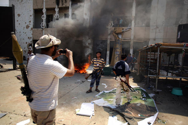 Armed rebels take pictures in front of Gadhafi's heavily damaged compound.