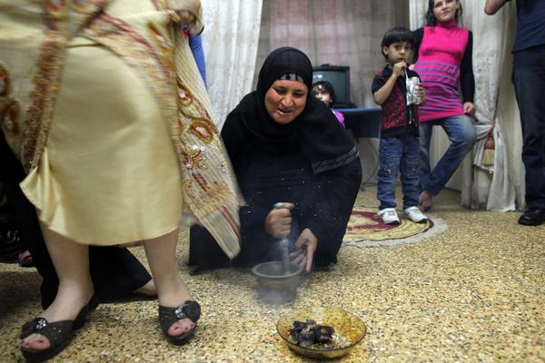A relative beats a mortar and pestle during the Sebou celebration for 7-day-old Hamza Ibrahim Muhammad in Mansoura, Egypt. Hamza's mother, Israa Saad Diab (in yellow), walks over a ritual offering and hot coals as part of the ceremony.