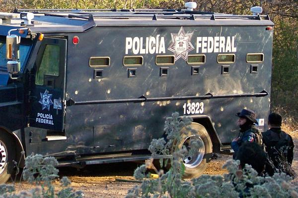 <b>Killed Dec. 9, 2010:</b> Nazario Moreno Gonzalez, the founder and leader of the cultlike La Familia cartel, is slain by federal police after a two-day shootout. Federal police officers stand near a bullet-riddled vehicle a day after the operation in Apatzingan, Mexico.