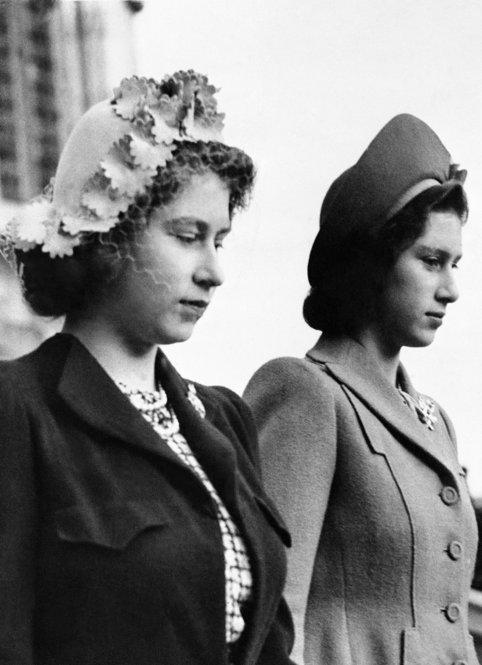 In this 1945 picture, Princess Elizabeth (left) wears a left halo hat trimmed with flower designs as she stands next to her sister, Princess Margaret Rose, during the wedding of Diana Piers Legh and the Earl of Kimberley at Windsor Castle in London.
