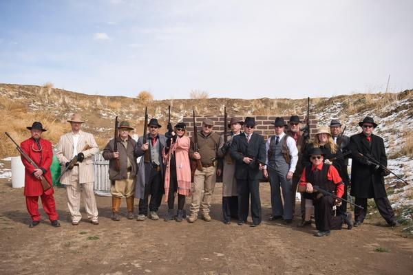 """Members of the Colorado chapter of the American Zoot Shooters set up """"capers"""" — shooting scenarios that allude to Prohibition-era Chicago gangsters, each featuring different rules and target arrangements. Here, they pose before the first """"caper"""" of the day on April 10, in Byers, Colo."""