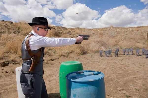 """Robert Fowler, aka """"John Smith,"""" demonstrates a two-handed shooting technique, a'la """"Road to Perdition,"""" just for fun after the second caper. Shooters are not allowed to shoot with both hands during a match for safety reasons."""