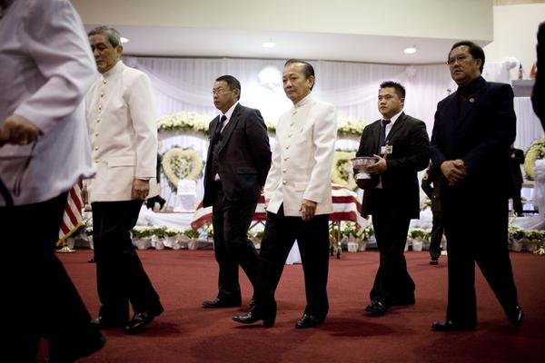 Prince Bouavong Kattygnarath (center) of the Lao royal family passes Vang's casket. Foreign dignitaries, U.S. military officials and elected representatives were among the thousands who came to mourn the general.