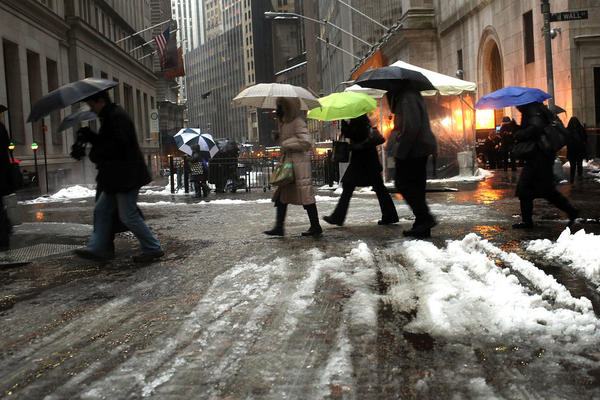 Pedestrians make their way through freezing rain during the morning commute along Wall Street on Wednesday in New York City.