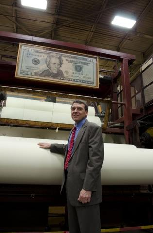 Crane & Co. Vice President Doug Crane stands near a spool of paper used for $20 bills, as it spins at the company's Wahconah Mill.