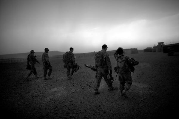 Soldiers walk through a driving rainstorm on the landing zone of Forward Operating Base Giro.