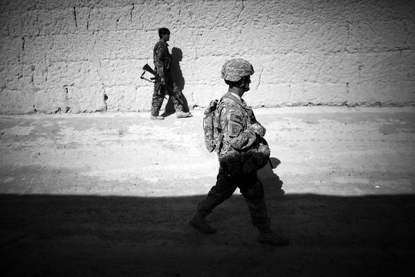 Sgt. 1st Class John Foster, with the Security Force Assistance Team attached to the 82nd Airborne, walks with an Afghan National Army soldier between mud-walled compounds in Babaker.