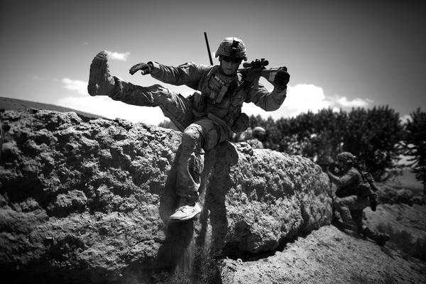 Staff Sgt. Laverne Schwartz takes up position as insurgent rounds hit the other side of a mud wall used for cover.