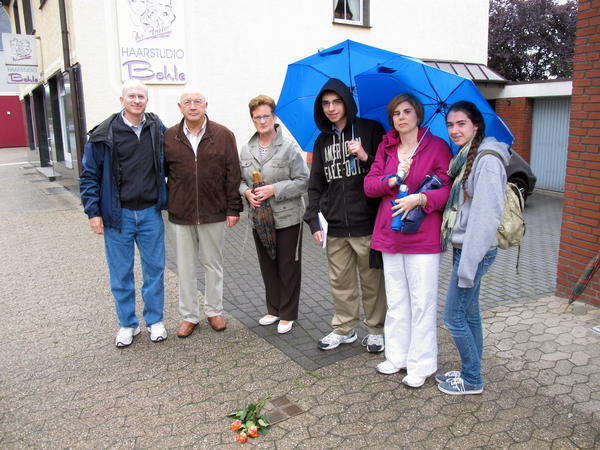 """Jeffrey Katz (far left), NPR's deputy managing editor for Digital News, stands next to """"stumbling stones"""" in Lembeck, Germany, that include names of family members evicted from their home during the Holocaust. With him, from left to right: Josef Langenhorst (who was age 7 when he saw the family being removed);  Langenhorst's wife; and Katz' family — son Ben, wife Mollie and daughter Emily."""