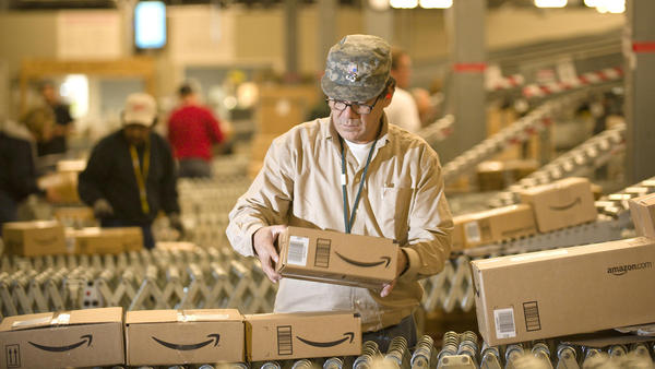 "An Amazon worker grabs boxes off a conveyor belt in Nevada, one of a <a href=""http://www.amazon.com/gp/help/customer/display.html/ref=hp_468512_which?nodeId=468512#which"">handful of states</a> in which the online retailer collects sales tax."