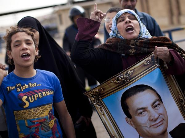 Supporters of Mubarak in Cairo chant slogans and carry his portrait as they demonstrate in February during his trial, outside the police academy.