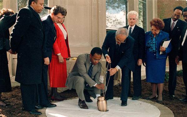 Baltimore Mayor Kurt Schmoke (center left) and NAACP Executive Director Benjamin Hooks lower the ashes of writer Dorothy Parker into her final resting place at the NAACP headquarters in 1988.