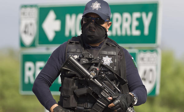 A Mexican federal policeman guards the area where dozens of bodies, some of them mutilated, were found on a highway outside the northern Mexican city of Monterrey on  May 13. The murders were one of the latest episodes in Mexico's brutal and unrelenting drug war.