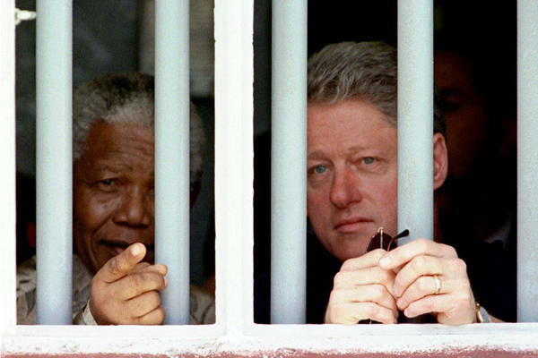 President Bill Clinton and Mandela peer through the bars of Mandela's prison cell on Robben Island, on March 27, 1998. Mandela spent 18 years in the cramped gray cell.