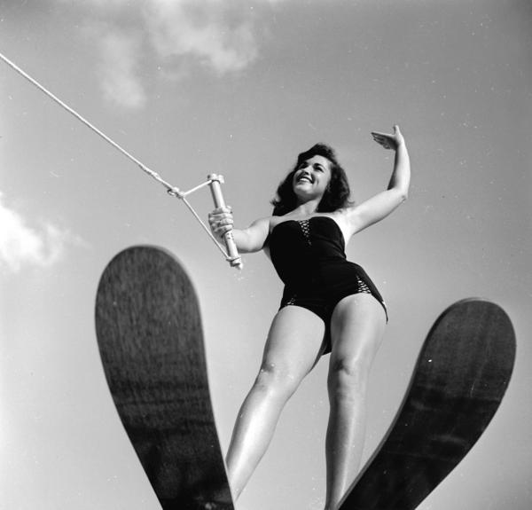 A swimsuit model poses on water skis while still on dry land in 1955.