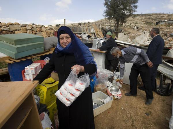 Palestinians collect their belongings after Israeli bulldozers raze their house in an Arab neighborhood in east Jerusalem on Feb. 9.