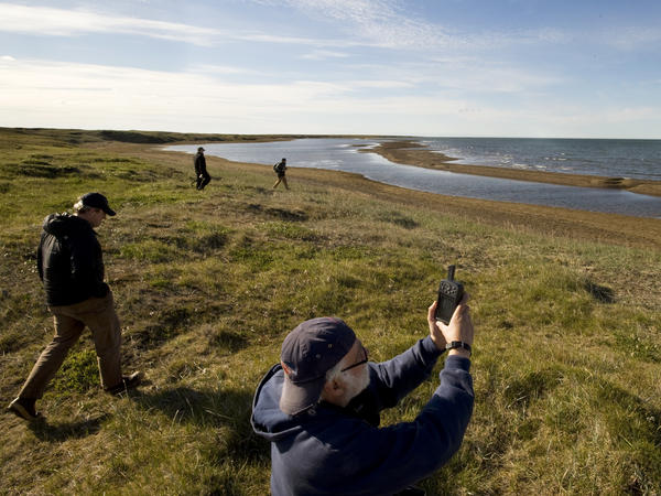 Richard E. Reanier, an independent archaeologist working for Shell Oil, uses GPS to record the location of the remains of a sod house along the Chukchi Sea coast near Wainwright, Alaska, in July 2011.