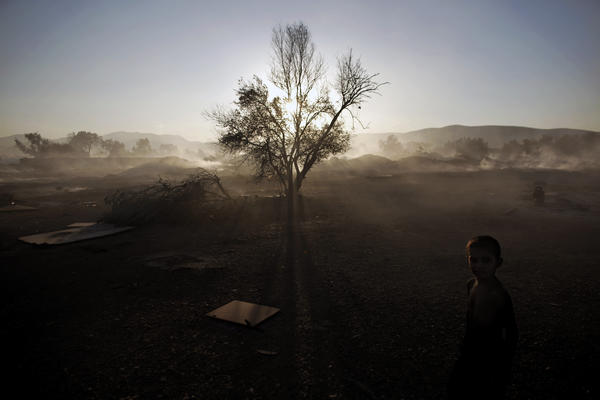 A Roma boy stands at a burnt Roma encampment, where the fire broke out in the industrial zone of Athens on Wednesday.