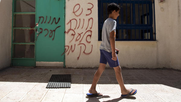"""A boy walks past spray-painted graffiti that reads in Hebrew, """"Death to Arabs"""" and """"Revenge."""" The vandalism took place earlier this month in the mixed Arab-Jewish community of Neve Shalom in Israel."""