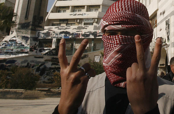 A Syrian youth flashes the victory sign as he stands in front of a building that was covered with anti-government graffiti — though local authorities painted over it — in the town of Duma, outside Damascus, in February.