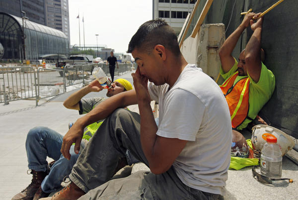 From left, construction workers Santiago Gomez, Jorge Moreno and Abel Lozano take a break from the extreme heat during a road construction project in downtown Chicago, Thursday. Little relief from the heat is expected in the next few days.
