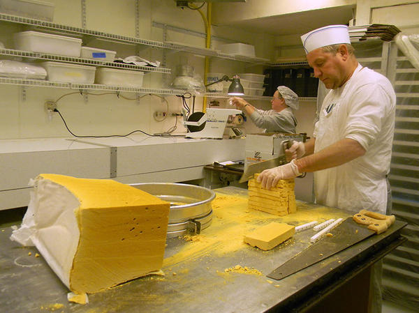 Candy maker Tim Leahy saws a block of sponge candy down to bite-size.