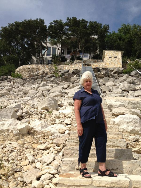 Connie Ripley stands 30 feet below the normal water line in front of her house on Lake Travis, which is half full because of the ongoing drought.