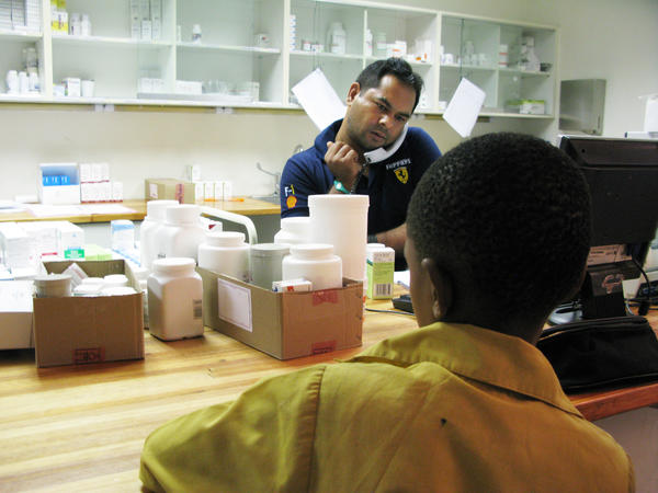 A boy waits to get his anti-AIDS drugs from pharmacist Rajesh Chandra at the Botswana-Baylor Children's Clinical Center of Excellence in Gaborone.