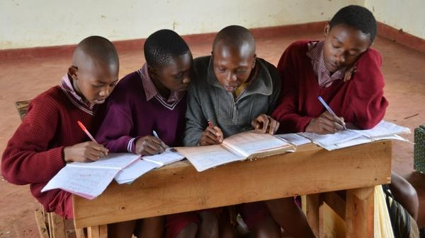Kenya has made its public schools free, which has dramatically increased the number of students. But this has also led to overcrowding. Here, four boys share a desk and a single textbook at the Amboni Secondary School in central Kenya.