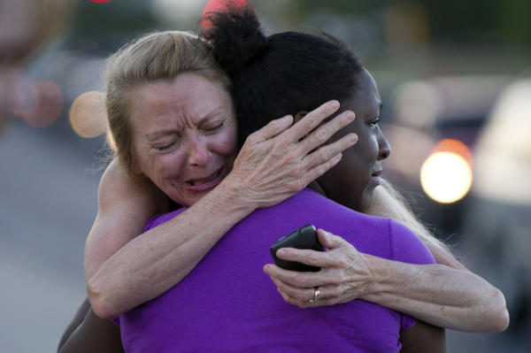 Two women mourn near the Century 16 theater in Aurora, Colo., where a gunman opened fire during the opening of the new Batman movie, <em>The Dark Knight Rises</em>.