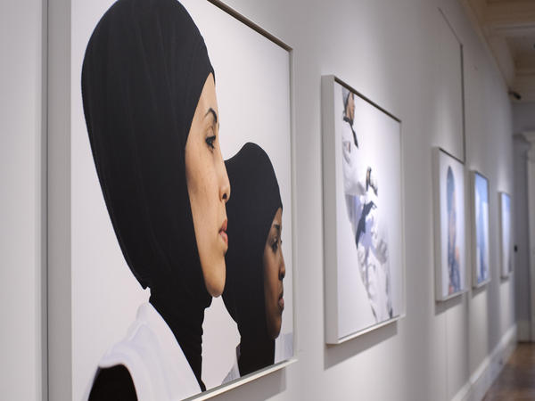 Photos hang at the opening of <em>Hey'Ya Arab Women In Sport</em> by Brigitte and Marian Lacombe at Sotheby's auction house in London.