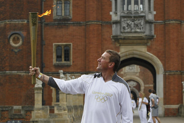 Four-time Olympic rowing gold medalist Matthew Pinsent poses with the torch at the courtyard of Hampton Court Palace in London on the final day of the torch relay.